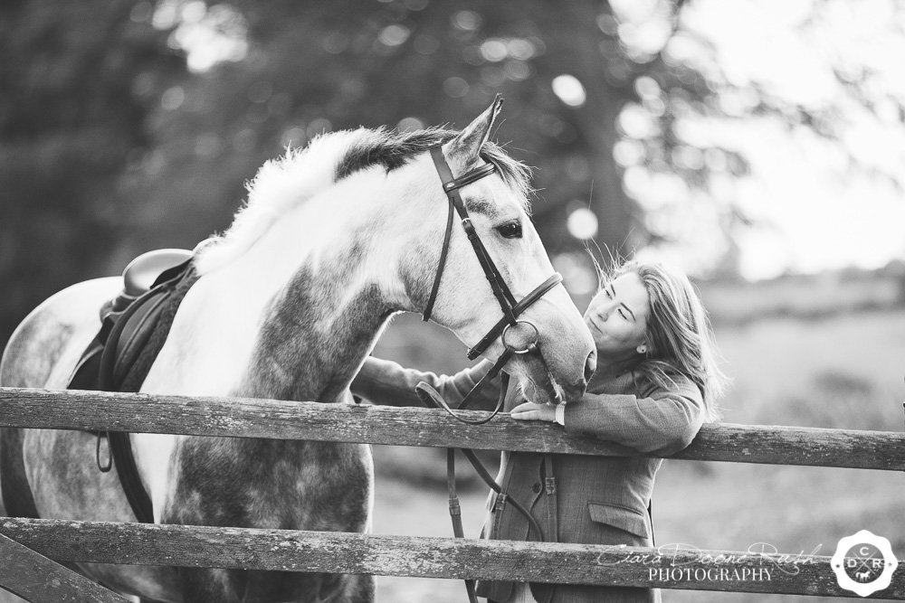 horse and rider leaning on a gate