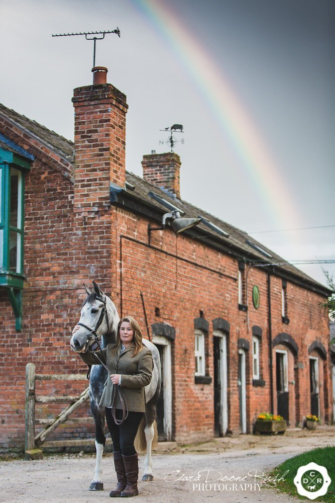 Horse and rider with a rainbow in a stable block