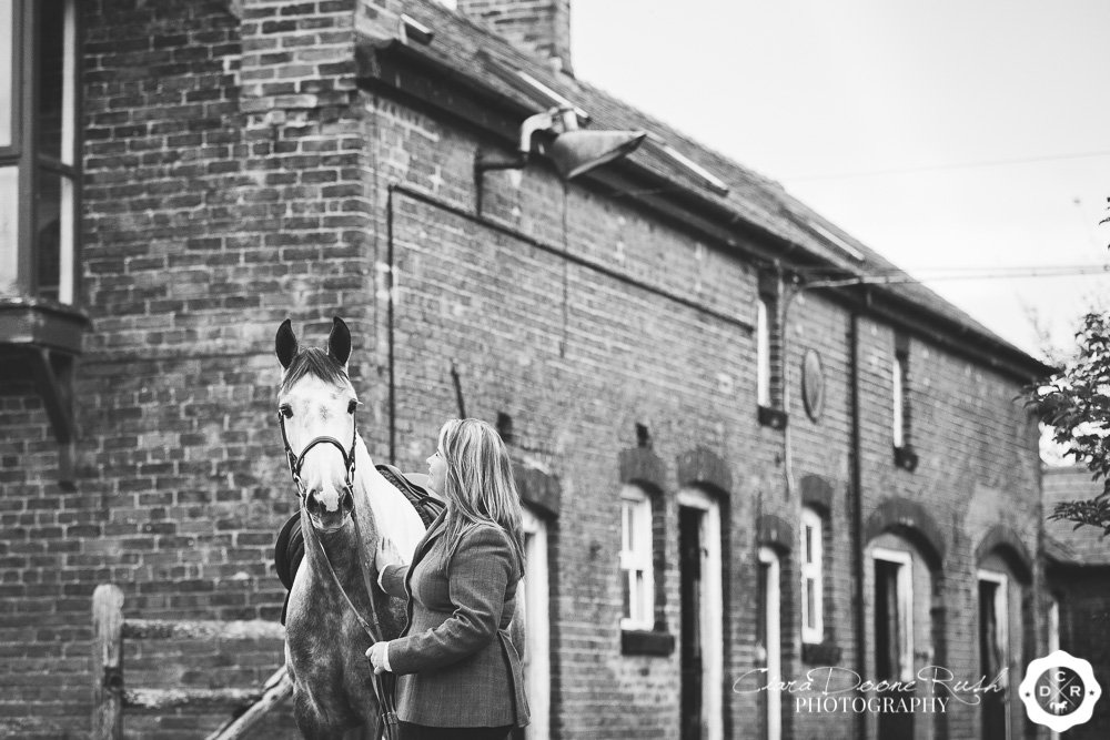 a rider and her horse in a stable yard