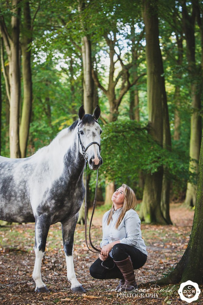 Girl crouching with horse