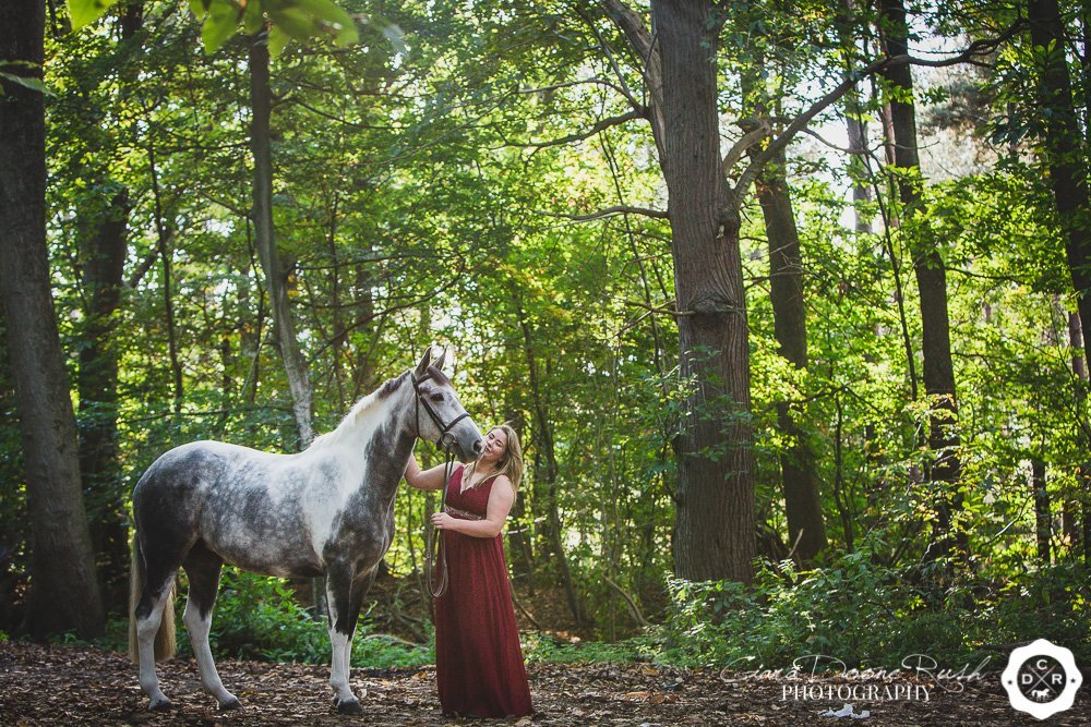 Horse and owner in forest