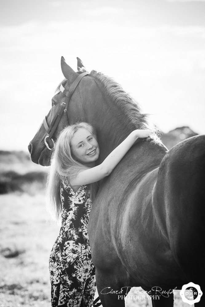 a girl hugging her pony