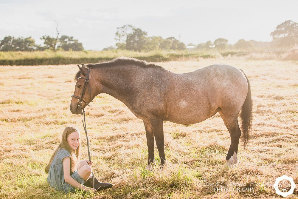a girl sat in a field with her pony