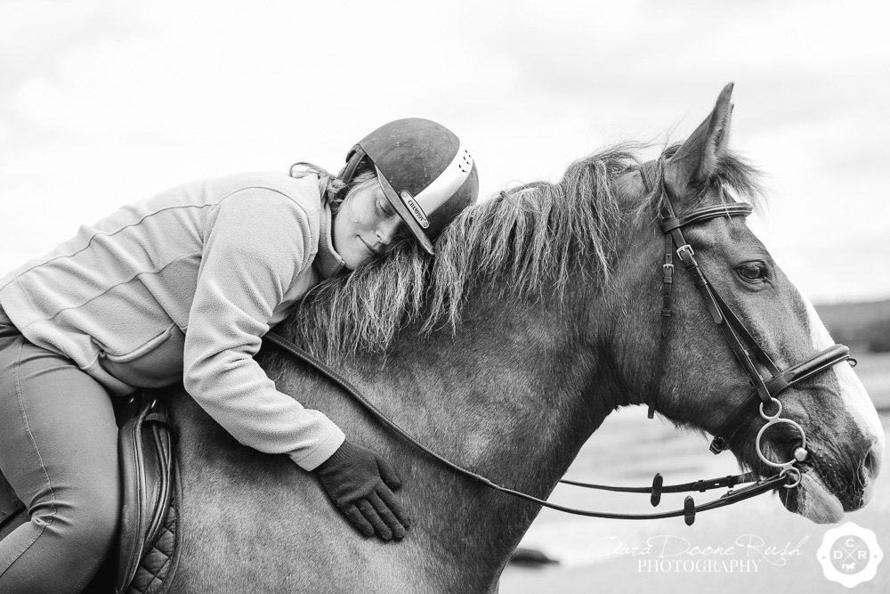 a girl hugging her horse