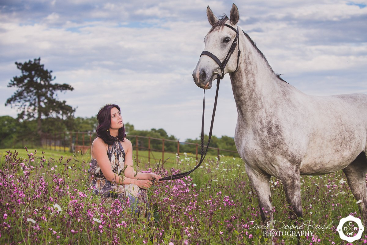 a woman and her horse sat in a field of flowers
