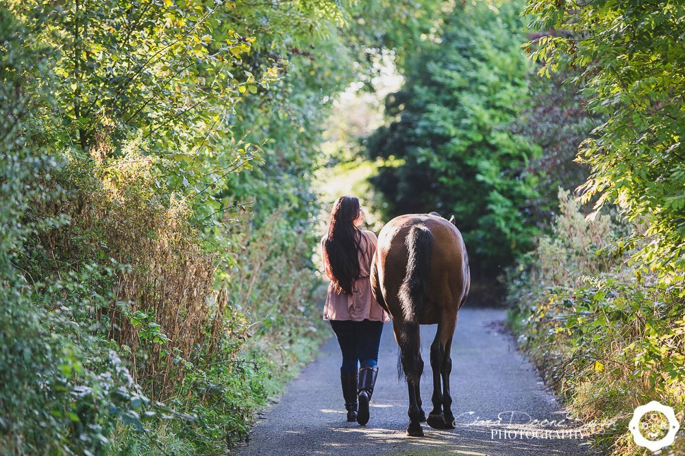 horse and rider walking down a lane on a photo shoot