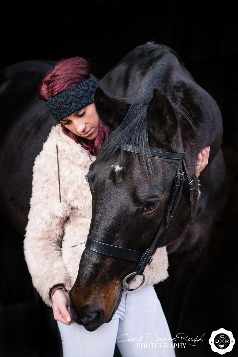 a black horse cuddling a woman