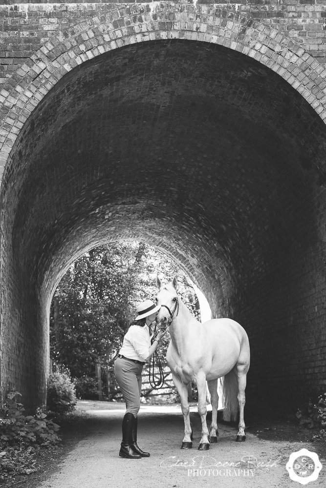 a woman and her horse on a photo shoot under a bridge