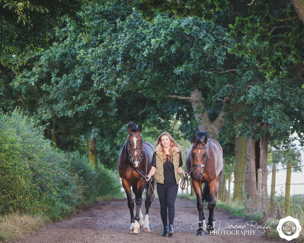 a girl leading her two horses down a track
