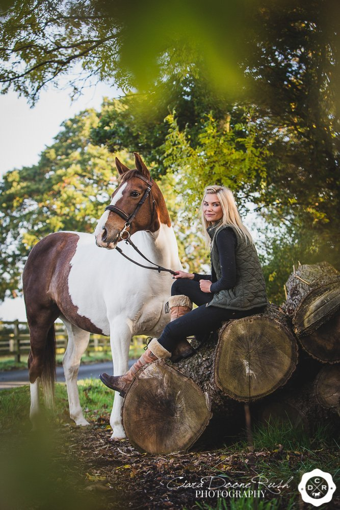 a woman and her horse sitting on logs