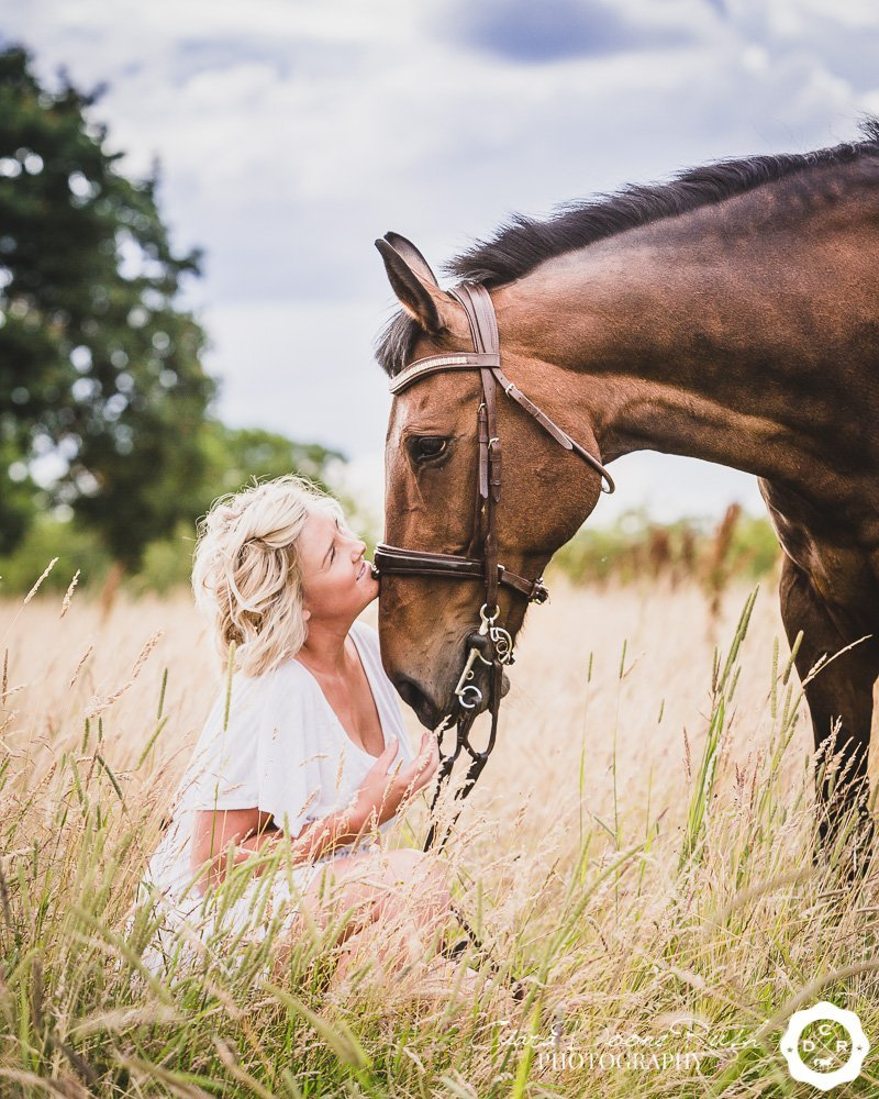 a woman and her horse in long grass