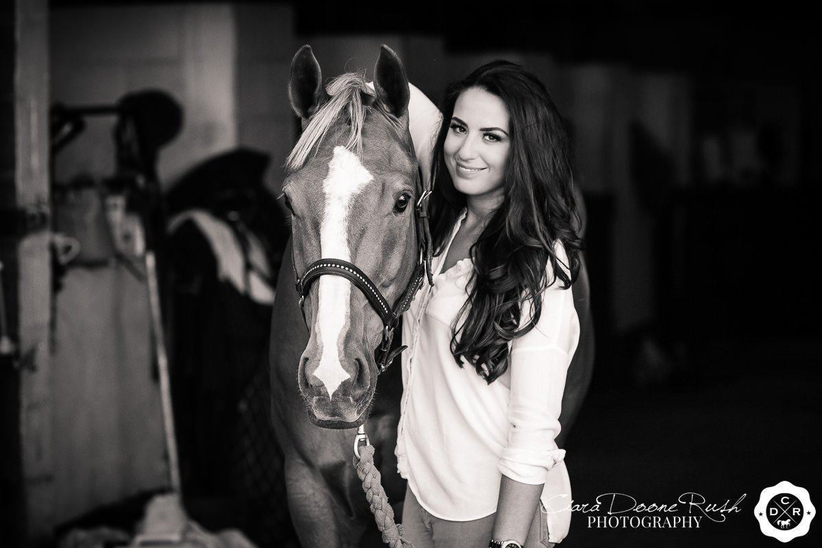 a black and white image of a woman and her horse