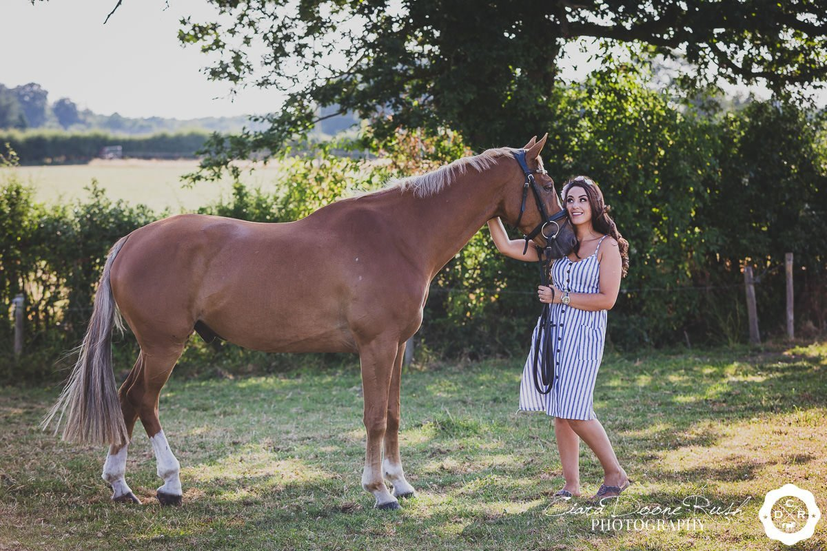 a horse cuddling it's owner on a summer evening horse and rider photo shoot