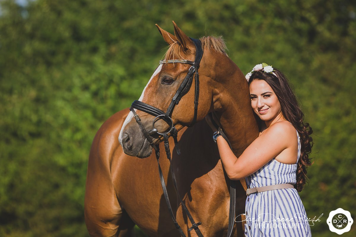 a woman hugging her horse's neck on a summer evening horse and rider photo shoot