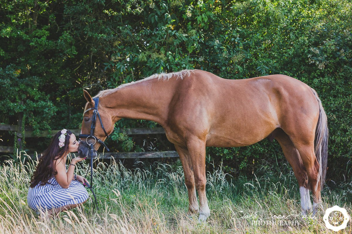 a woman in a long grass field kneeling by her horse on a summer evening horse and rider photo shoot