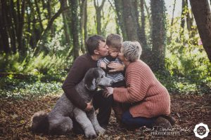 a kid being kissed by his parents on a family and animal photo shoot