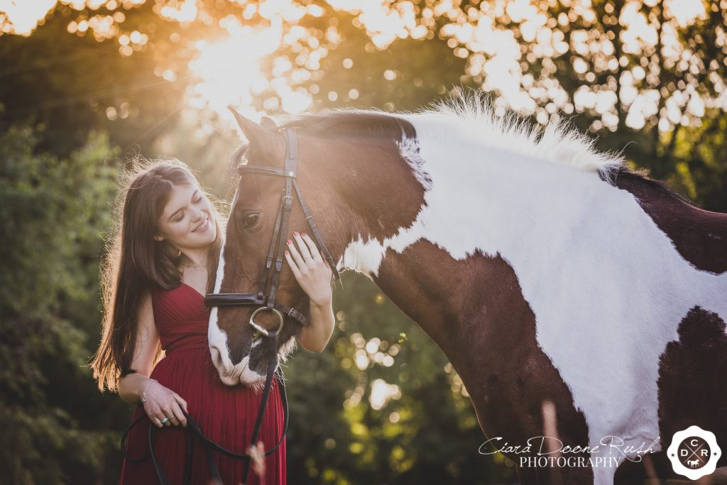 a teen and her horse in evening sunshine