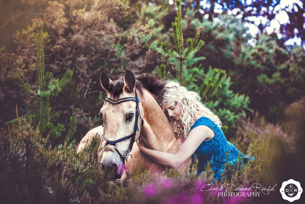 a girl and her pony lying in the bracken